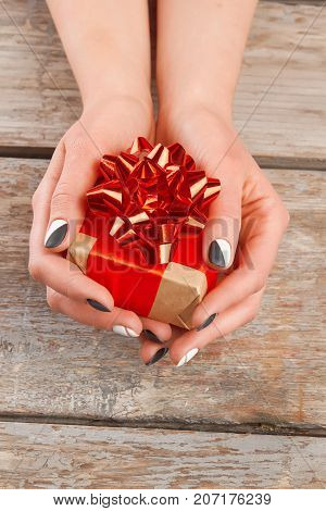 Manicured hands holding little gift box. Young woman hands with beautiful manicure and gift box, old wooden background.