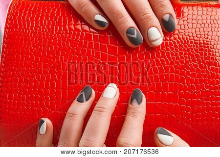 Elegant red ladies handbag in female hands. Trendy matte manicure and leather purse close up. Womans beauty and style.