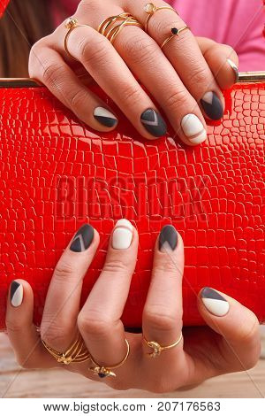 Well-groomed hands holding red handbag. Red lacqured clutch in female hands. Female manicured hands with luxury jewelry.