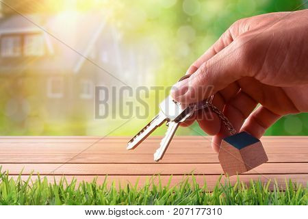 Hands With Home Keys On Table On Nature Purchase Concept