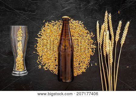 Grains of malting barley near beer bottle on black background top view. poster