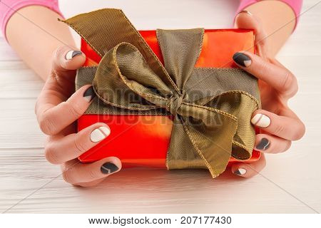 Gift box in female manicured hands. Woman hands with black and white manicure holding red box with gift. Holidays and celebrations concept.