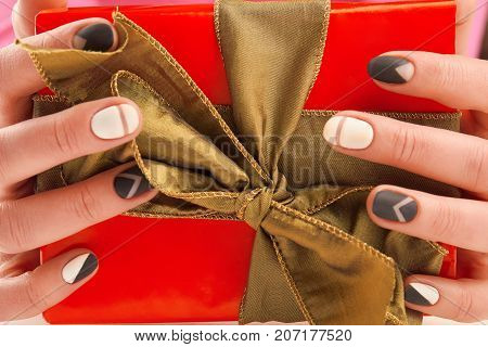 Stylish manicure and gift box close up. Female hands with fashion matte manicure holding red gift box close up. Female trendy nail design.