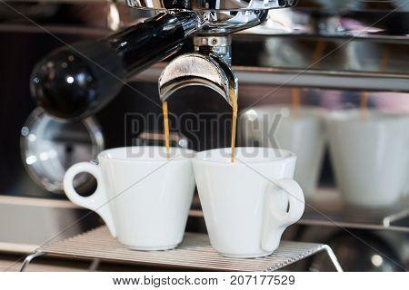 Two cups of espresso in the coffee machine. Subject of professional preparation of coffee, barista's secrets, invigorating fresh coffee, etc.