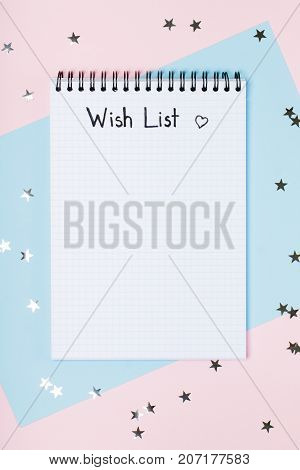 Notepad for wish list on a pink and blue background with stars. Concept of New Year or holiday dreams