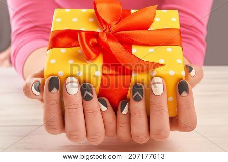 Manicured hands holding gift box. Close up of woman hands with matte manicure holding yellow gift box with red ribbon. Holidays and celebrations concept.