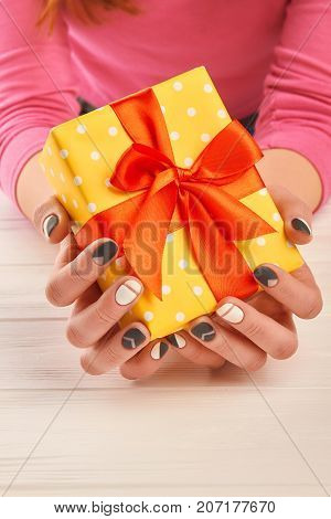 Hands with stylish manicure holding gift box. Female manicured hands holding yellow dotted box with gift on white wooden background. Holidays and celebrations concept.