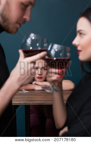 Sad left alone female in bar. Jealousy backdrop. Cheating relationships. Unhappy lonely woman in focus on blue background, loneliness concept