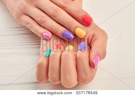 Female hands with stylish summer manicure. Woman hands with colorful nail polish close up. Well-groomed hands with bright manicure on wooden background.