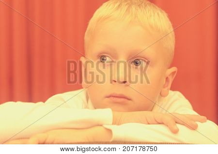 A shoulder portrait of a small boy sitting on a chair with a thoughtful face