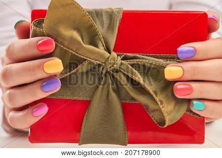 Gift box in manicured female hands. Woman hands with multicolored summer nails holding red gift box close up. Beautiful summer manicure.