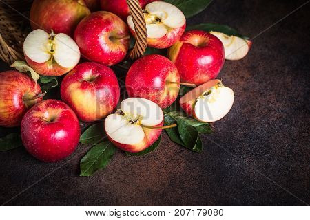Whole and sliced red apples scattered from the basket on the dark rustic table.