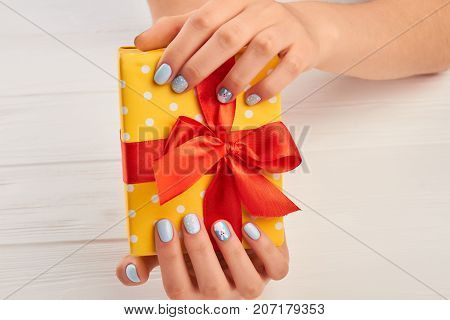 Yellow gift box in female hands. Beautiful woman manicured hands with gift box. Box with gift and winter fashion manicure.