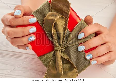 Female manicured hands holding gift box. Woman hands with winter nails design holding Christmas gift box. Holidays and celebrations concept.