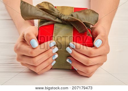 Gift box in well-groomed female hands. Young woman hands with gentle winter manicure holding box with gift. Perfect winter nail design.