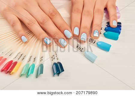 Manicured hands and nail color samples. Female hands with perfect winter manicure on nails color palette. Woman in nail salon. Variety of winter colors nail samples.