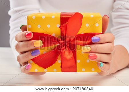 Summer manicure and yellow gift box. Woman hands with multicolored varnish on nail holding bright box with gift close up. Holidays and celebrations concept.