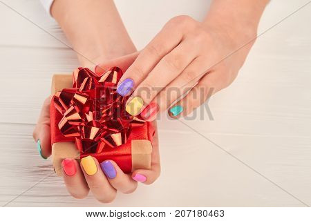 Handmade gift box in female hands. Beautiful woman hands with summer manicure holding little gift box with red bow. Multicolored summer manicure.