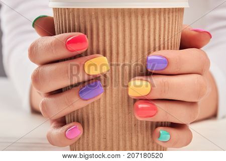 Cardboard cup in female hands close up. Woman hands with multicolored summer manicure holding disposable cup close up. Stylish summer manicure.