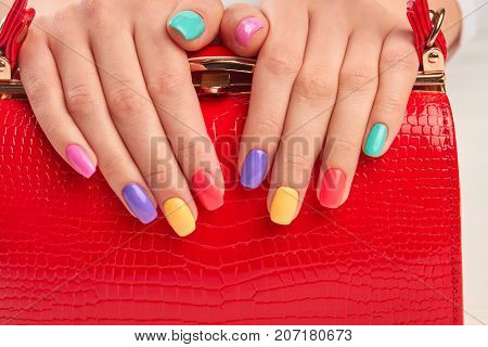 Multicolored manicure and expensive red handbag. Modern style colorful manicure on red leather handbag. Female manicured hands on red lacquered handbag.