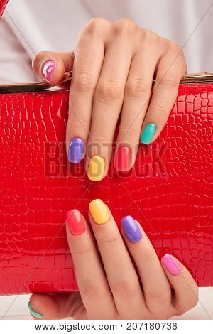 Multicolored nails and red leather handbag. Hands with beautiful summer manicure holding red lacquered handbag close up. Woman beauty and style.