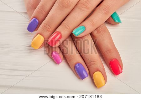 Multicolored manicure close up. Young woman hands with pastel manicure on white wooden background. Summer fashion manicure.