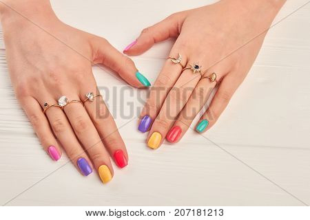 Manicured hands of young woman. Summer manicure and many rings with precious stones on female hands. Fashion manicure and luxury jewelry.