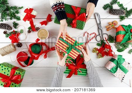 Creative diy hobby and online shopping background. Top view on female hands at messy table surface with christmas ornaments, ribbons, present boxes, mobile and credit card