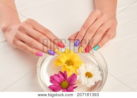 Manicured hands on glass bowl with water. Young woman hands with colorful nails receiving spa treatment. Aroma therapy for female hands.
