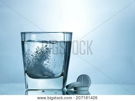 Effervescent tablet in a glass with bubble. medicine pill background