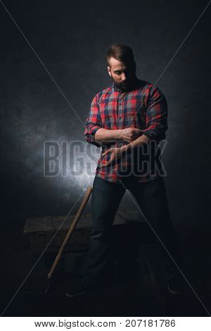 Strong rural worker on dark background. Thoughtful adult lumberjack, powerful male. Gloomy atmosphere, man strength, craftsmanship concept