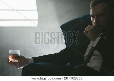 Rich people leisure with alcohol and vape. Modern businessman in private club, male bad habits. Smart look in focus on foreground, luxury life with whiskey and smoking