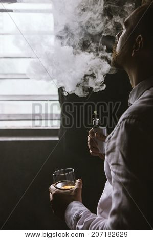 Pensive looking male in relaxed mood. Man leisure with alcohol and vape in private club, bad habits. Luxury life with whiskey and smoking, dark place background