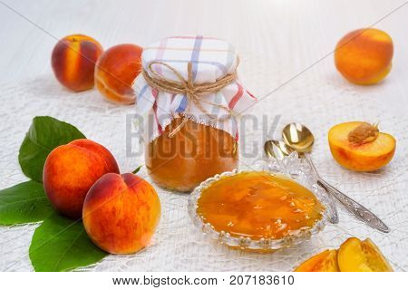 Jam of peaches on the table in a jar, next to a bowl of jam and spoons, peaches