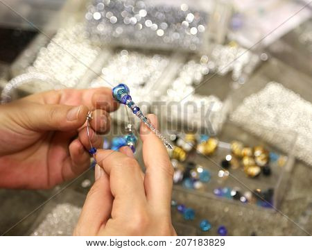 Hand of handy handmade woman as she wraps beads in craft bracelet