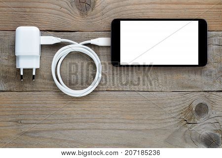 Charger and smartphone on wooden table top view