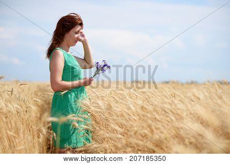 Woman on golden wheat field in summer