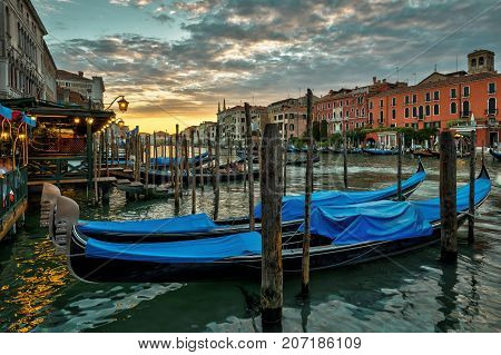 Grand Canal with gondolas at sunset in Venice, Italy. Grand Canal is one of the major water-traffic corridors in Venice.