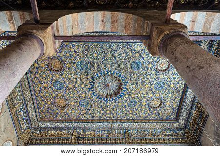 Cairo, Egypt - April 1, 2017: Ornate ceiling with blue and golden floral pattern decorations framed through huge arch and two columns at Sultan Barquq mosque Al Moez Street Old Cairo