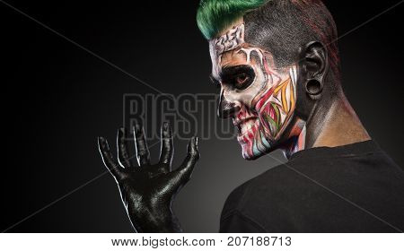 Side view of a man with monster face make up and hand painted in black. Mystical face art, man with skull makeup.