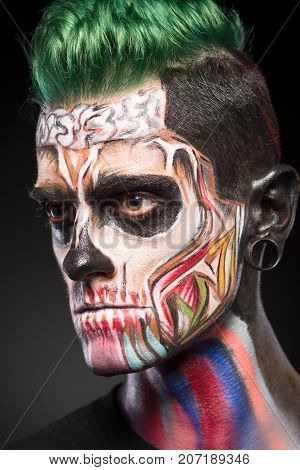 Close up portrait of zombie makeup on mans face. Mystical face art, monster face isolated on black background.
