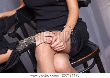 Women are holding hands. Close-up photo of young coupleThere are two woman on the photo. One of them is sitting on a chair. Other young woman is standing alongside. She is stroking her girlfriend's thigh.
