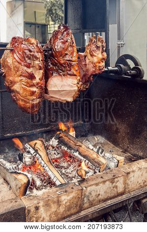 A spit for cooking roast shank in Prague on a Sunny day. National cuisine. The street food. The vertical frame.