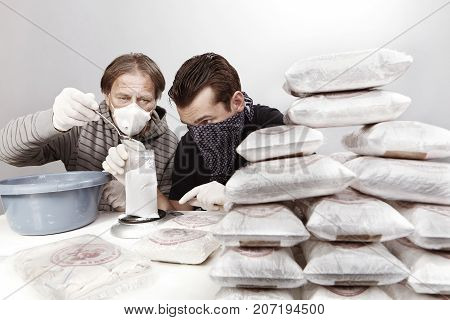 Two dealers preparing lot of drugs for distribution