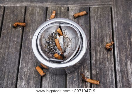 Cigarette butts with ash in ashtray on grey wooden table.
