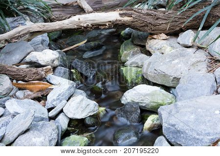 small creek time lapse shot with stones and wood water running down