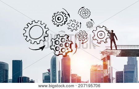 Businessman in suit drawing sketches of gear mechanism while standing on broken bridge with cityscape and sunlight on background. 3D rendering.