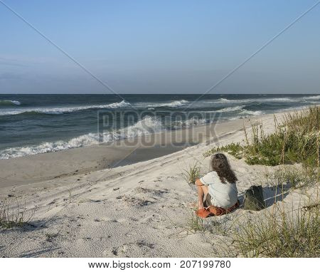 Backview of woman seated on sand dunes at Florida beach gazing out to sea at waves and crashing surf.