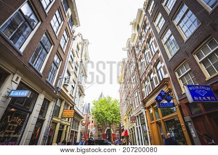 AMSTERDAM NETHERLANDS - JUNE 21 2016: A street full of commercial buildings with restaurants salons and jewelry stores in a cloudy day. Amsterdam Netherlands.