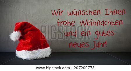 Gray Grungy Cement Wall With German Text Wir Wuenschen Ihnen Frohe Weihnachten Und Ein Gutes Neues Jarh Means We Wish You A Merry Christmas And A Happy New Year. Sanat Hat For Seasons Greeting Card.